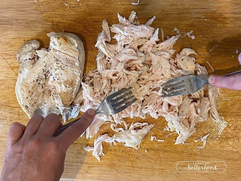 chicken breast on cutting board with forks shredding chicken