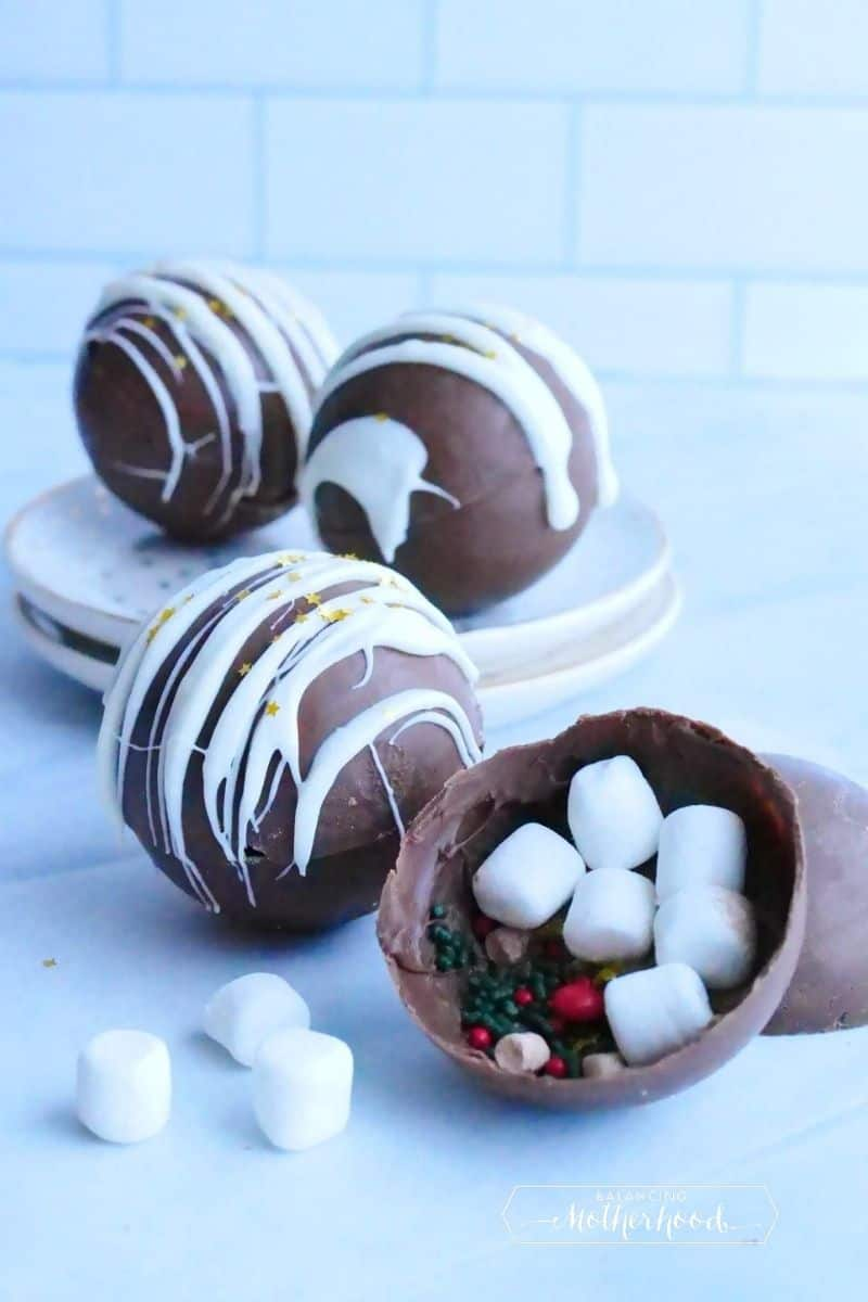 How chocolate bombs. One is left open to show marshmallows and sprinkles inside.
