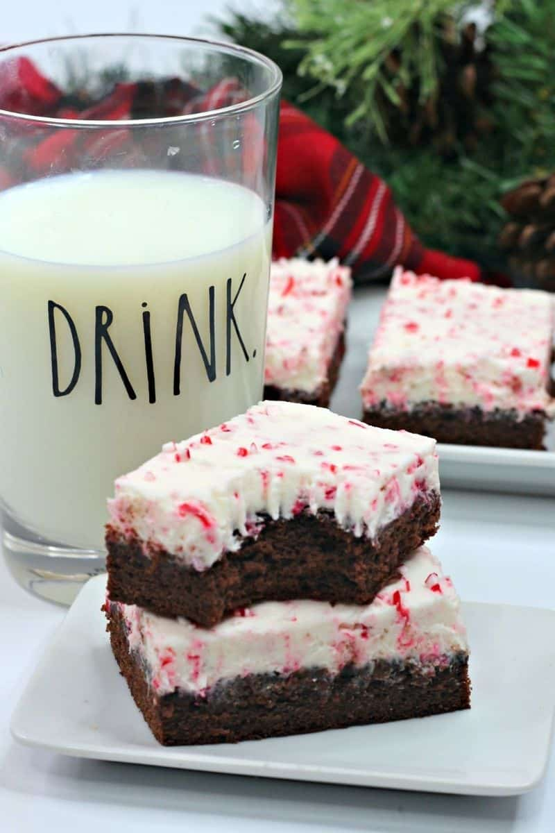 two brownies stacked on top of each other with a glass of milk