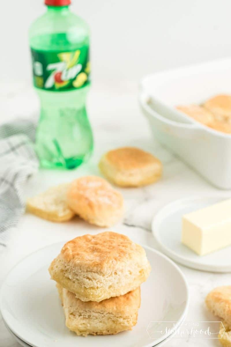 two biscuits stacked on plate with butter, and 7UP in the background