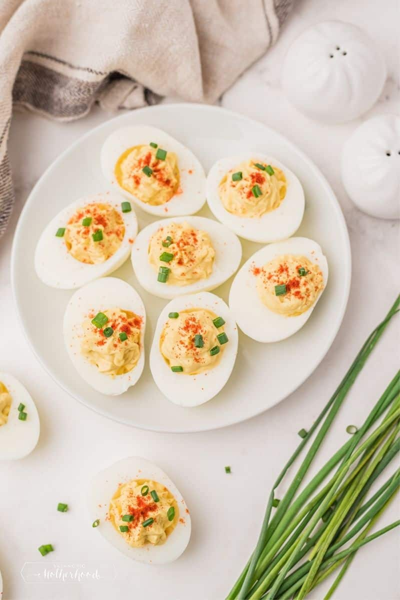 deviled eggs with paprika and chives on white counter