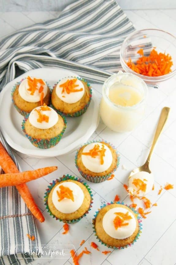 carrot cake cupcakes with frosting. carrots on the table with carrot shavings