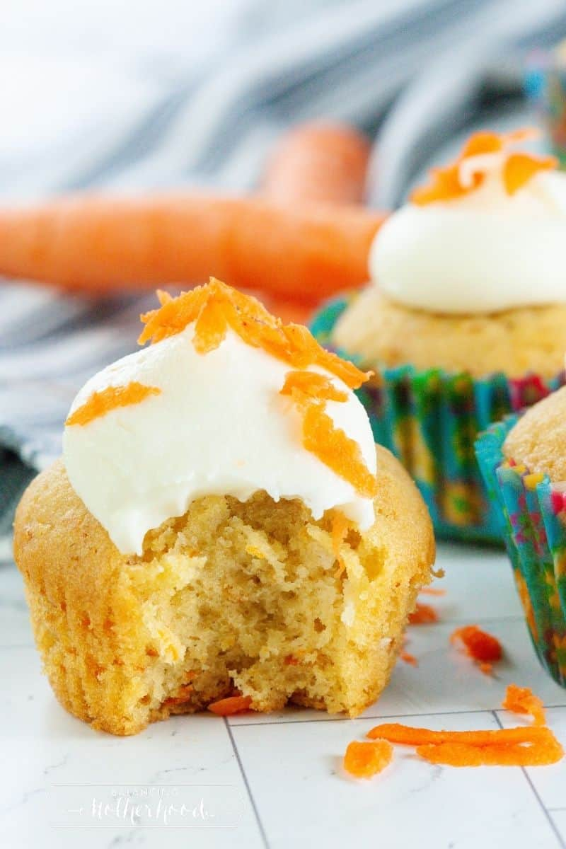 cupcake with bite out topped with dollop of cream cheese frosting and carrot garnish