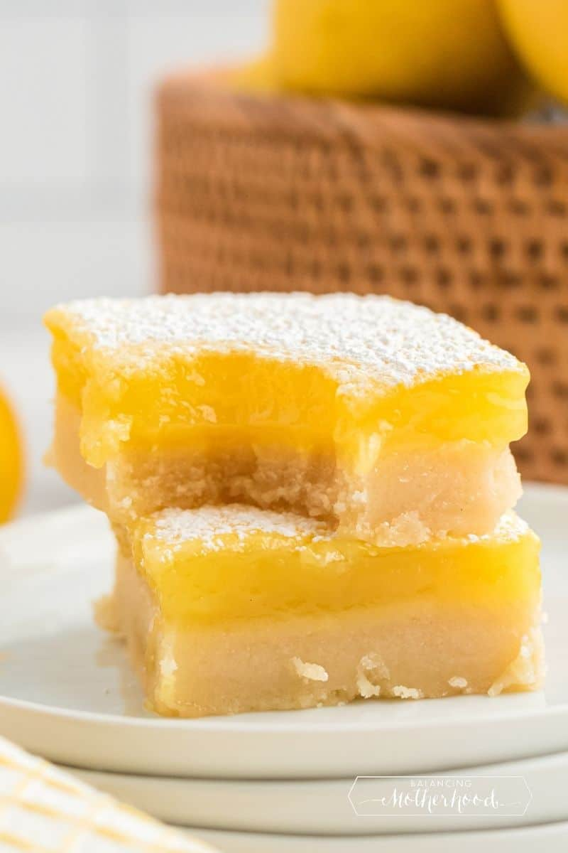 two lemon bars stacked, top one has bite out