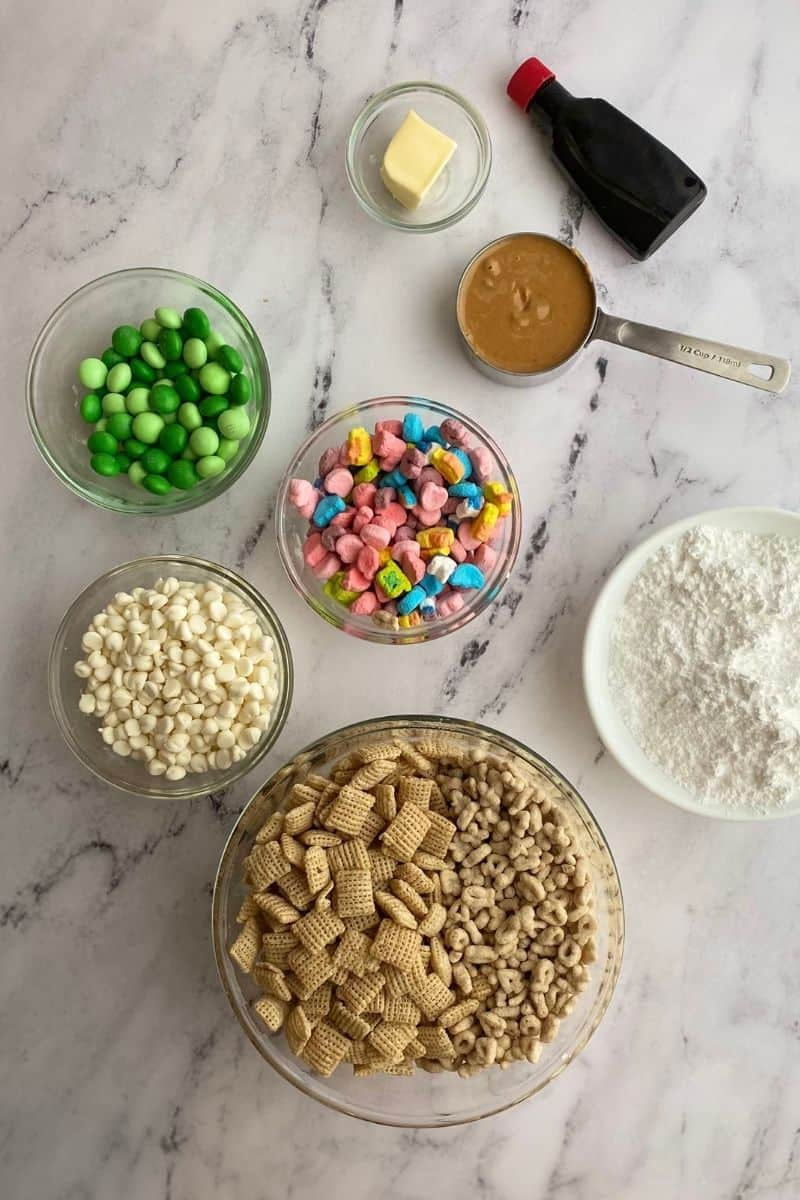 lucky charms muddy buddy ingredients: green M&Ms, white chocolate chips, Chex cereal, lucky charms cereal, lucky charms marshmallows, peanut butter, butter, vanilla