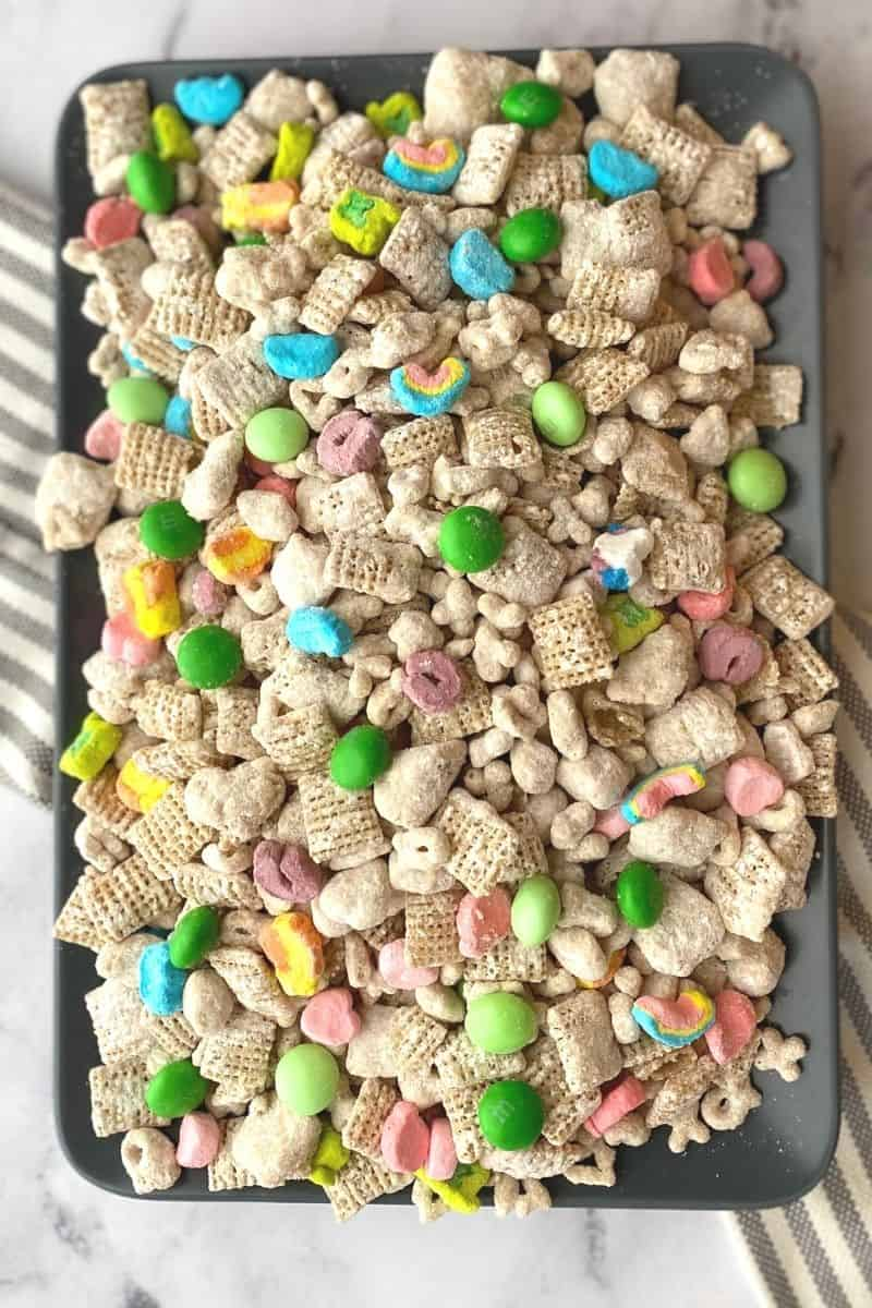 plate topped with a heaping pile of Lucky Charms muddy buddies with green m&ms and Lucky Charms marshmallows