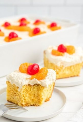 two pieces of yellow cake with frosting and mandarin oranges