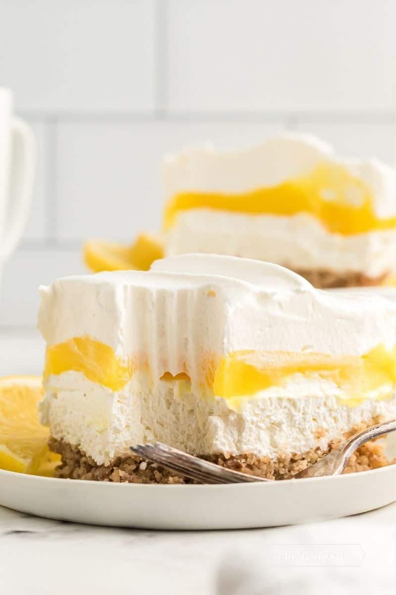 slice of lemon lush where you can see the pecan crust topped with a white layer, then a bright yellow layer all topped with whipped cream