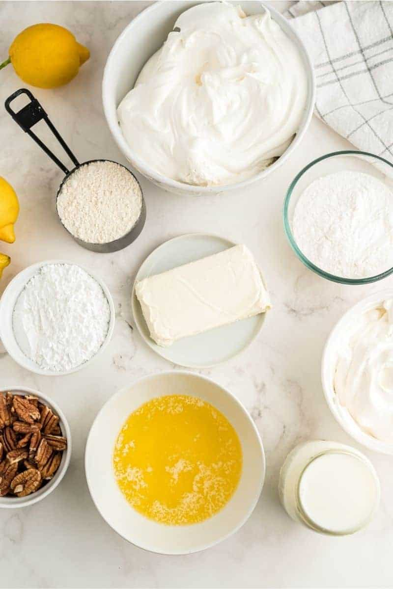 ingredients on table: whipped cream, flour, lemon pudding, cream cheese, powdered sugar, melted butter, and a glass of milk