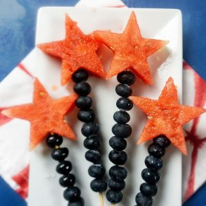four skewers on plate with watermelon star on top and blueberries down the skewer