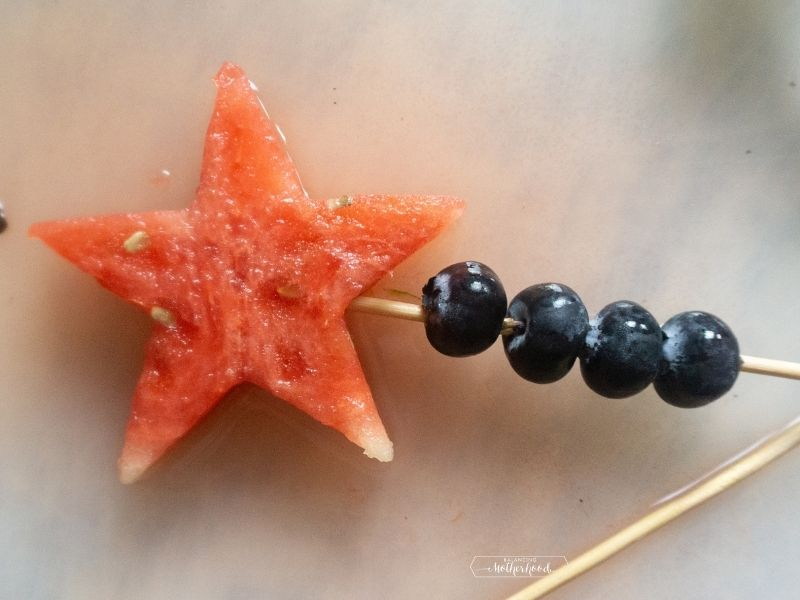 watermelon star on top of a skewer with some blueberries on bottom of skewer