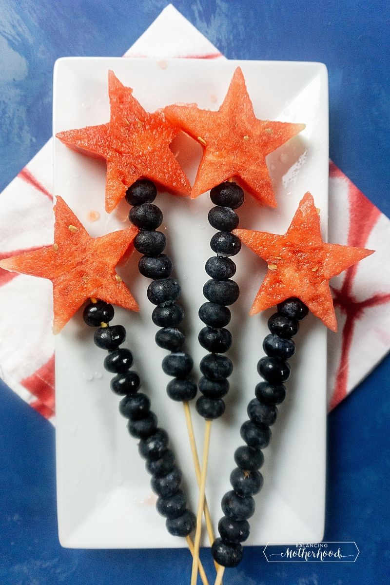 four watermelon starts with blueberries on a skewer on a white plate