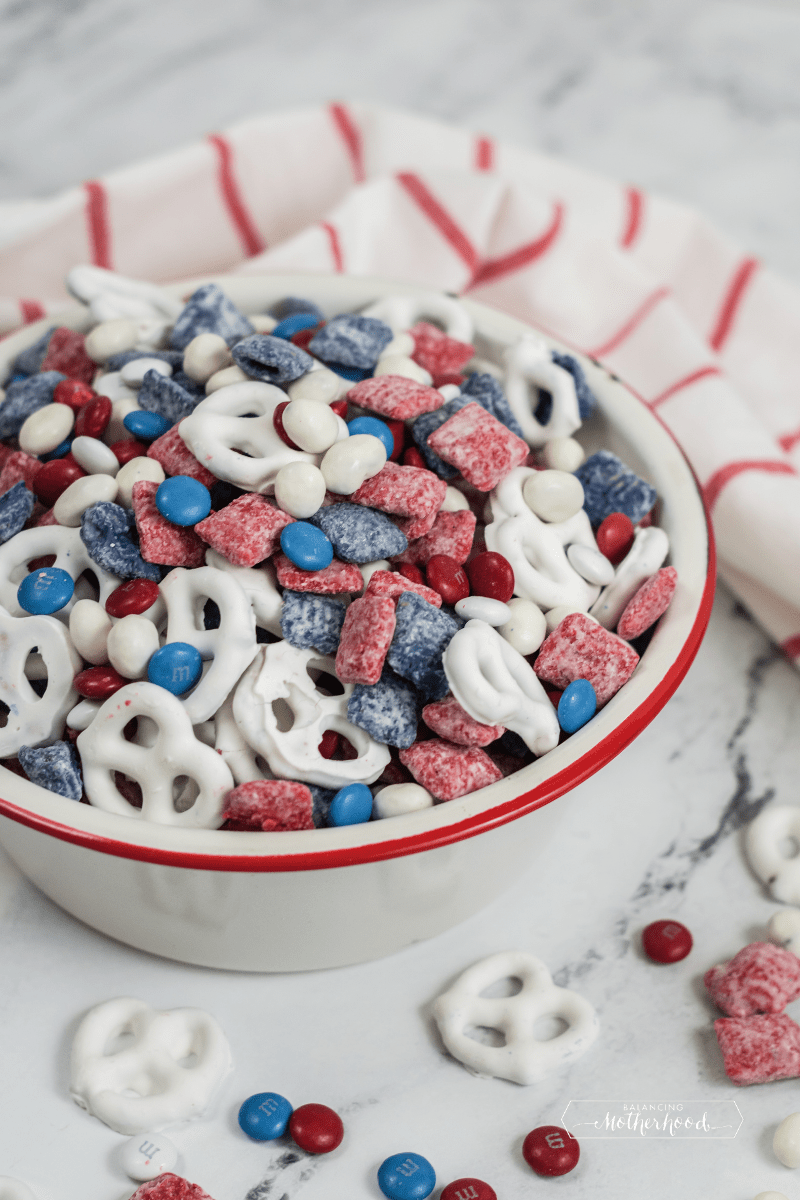 white pretzels with red and blue coated cereal and red, white, and blue M&Ms in white bowl with red and white tea towel on counter