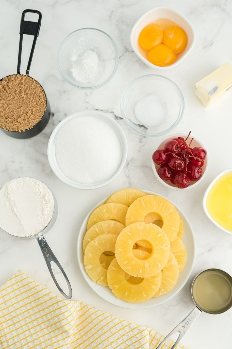 ingredients: brown sugar, butter, pineapple slices,  eggs, sugar, flour, salt, and cherries with a yellow and white checkered cloth