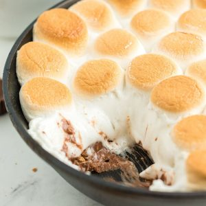 skillet with golden marshmallows and melted chocolate