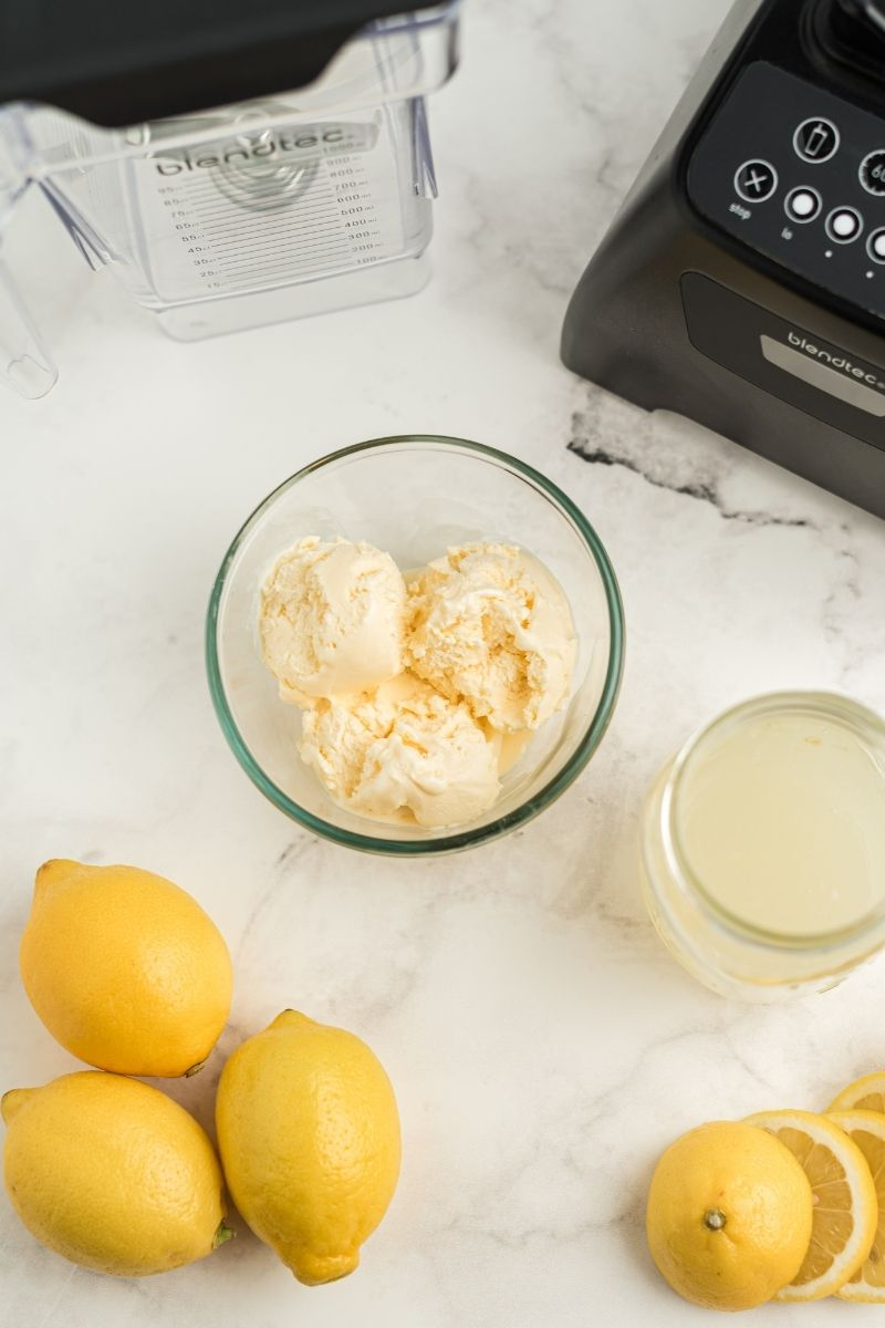 blender, vanilla ice cream in glass bowl, glass of lemonade and lemons on counter