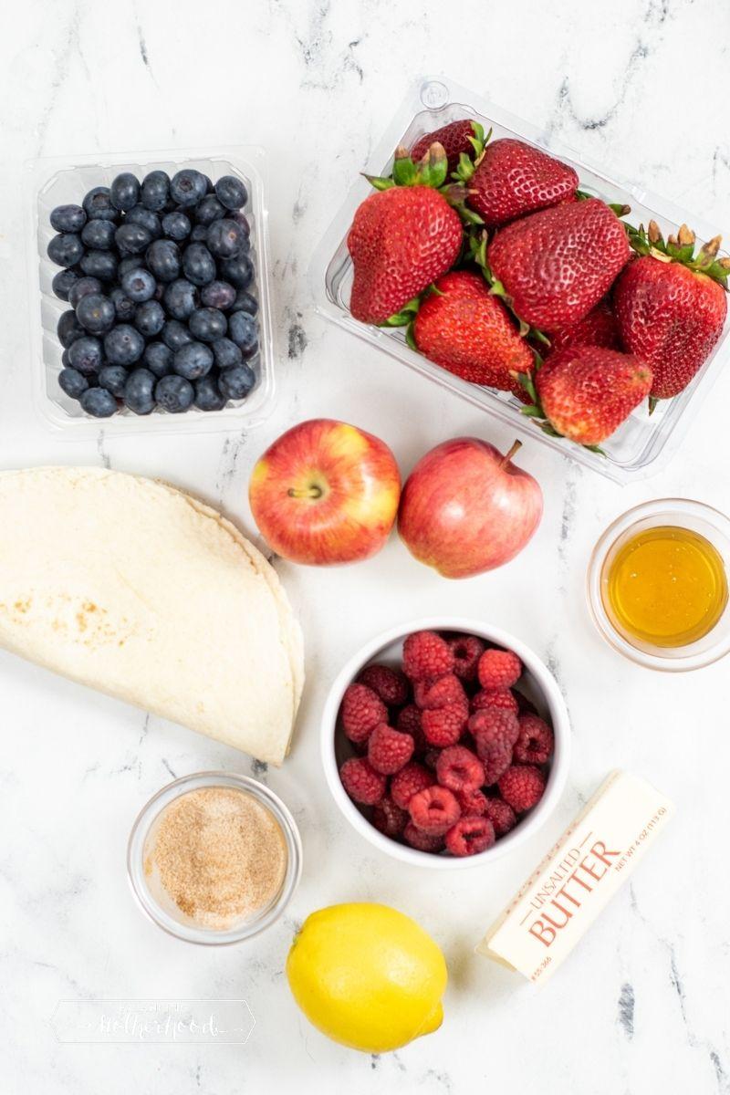 ingredients on white counter: tortillas, raspberries, cinnamon sugar, lemon, butter, honey, apples. strawberries, blueberries
