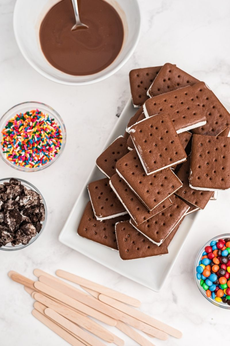 white counter with ingredients: bowl with magic shell, rainbow sprinkles, ice cream sandwiches cut in half, mini M&Ms