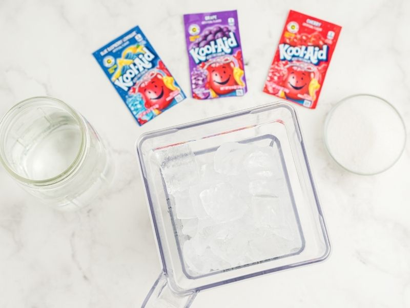 white counter with ingredients: three Kool-Aid packets, blue, purple and red, bowl of sugar, blender with ice, mason jar with water