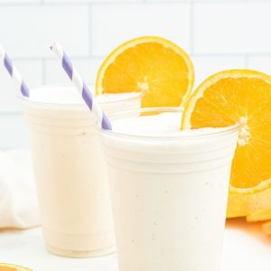two cups with white milkshake and orange slices