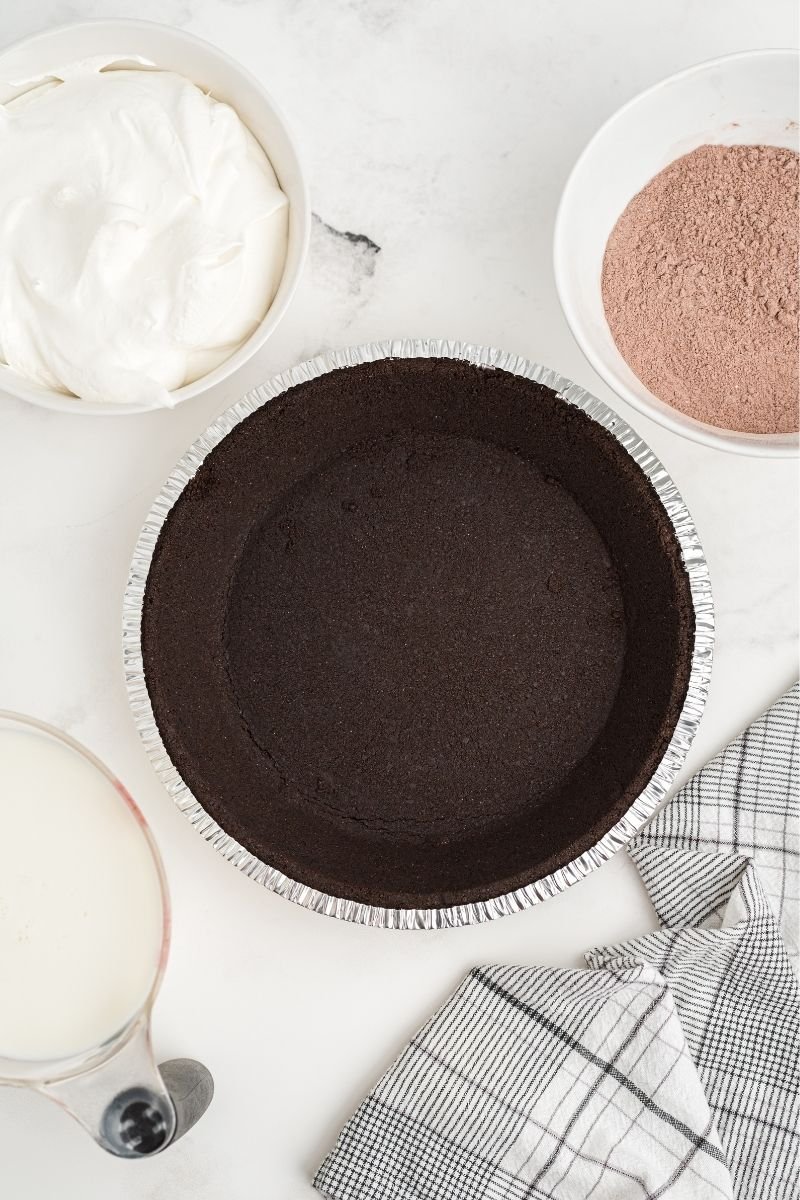 ingredients on white counter: Oreo pie crust, milk, Cool Whip, and powdered chocolate pudding mix