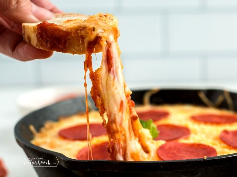 cheese being pulled from pan of pizza dip