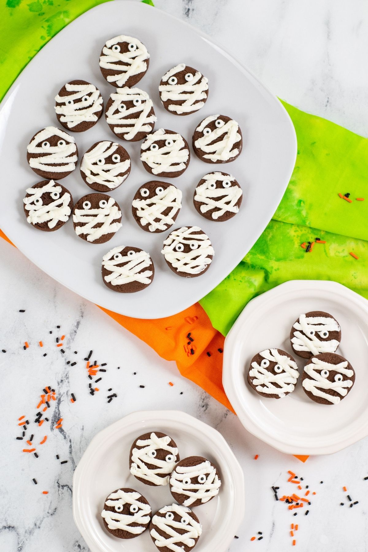round chocolate cookies with mummy buttercream stripes and candy eyes on white plates