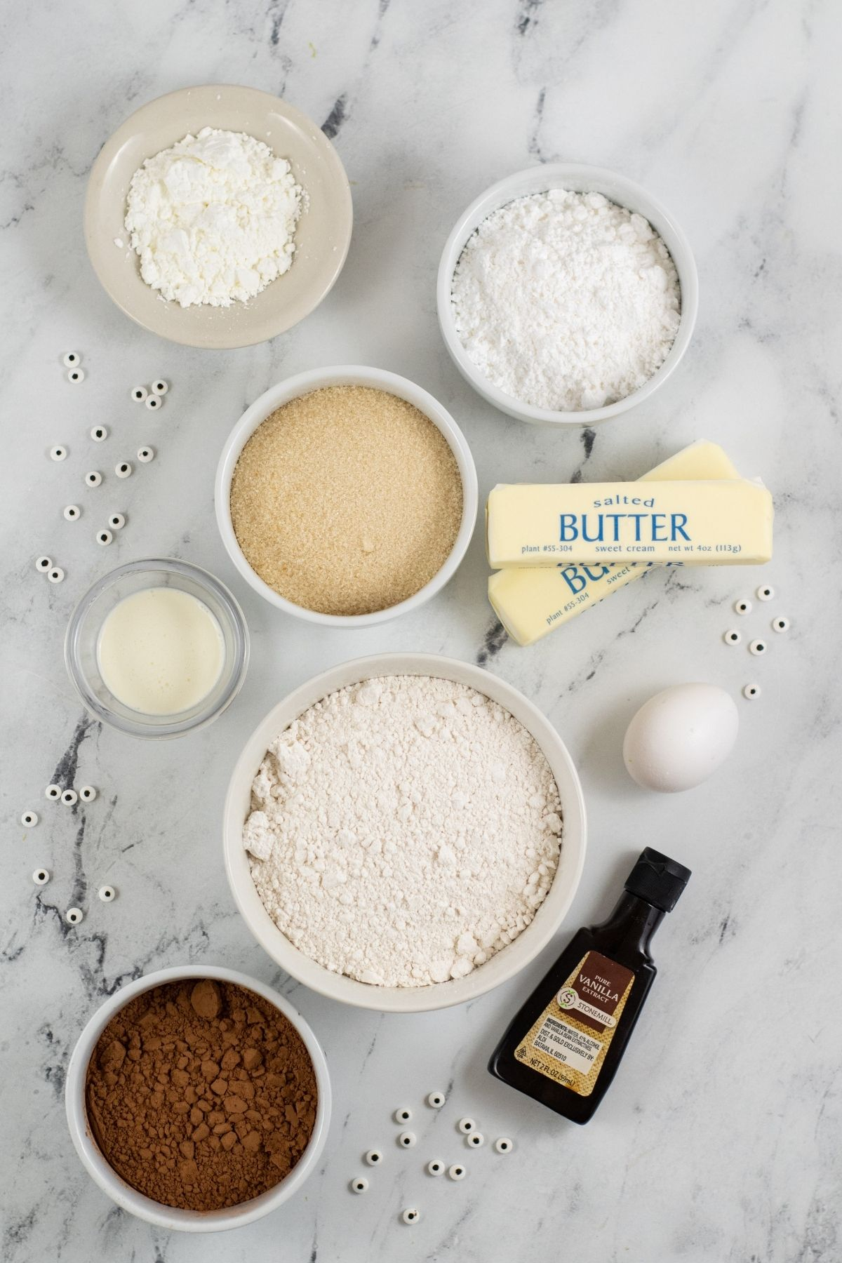 ingredients in white bowls on white counter: flour, corn starch, salt, cocoa, sugar, 2 sticks of butter, egg, vanilla, and candy eye balls