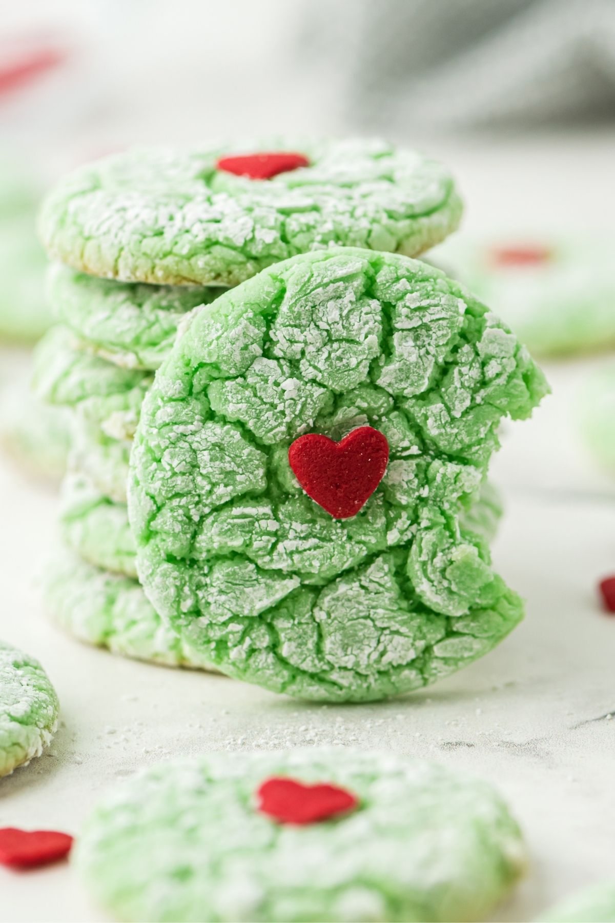 green cookie with red heart in the center and a bit out of the cookie