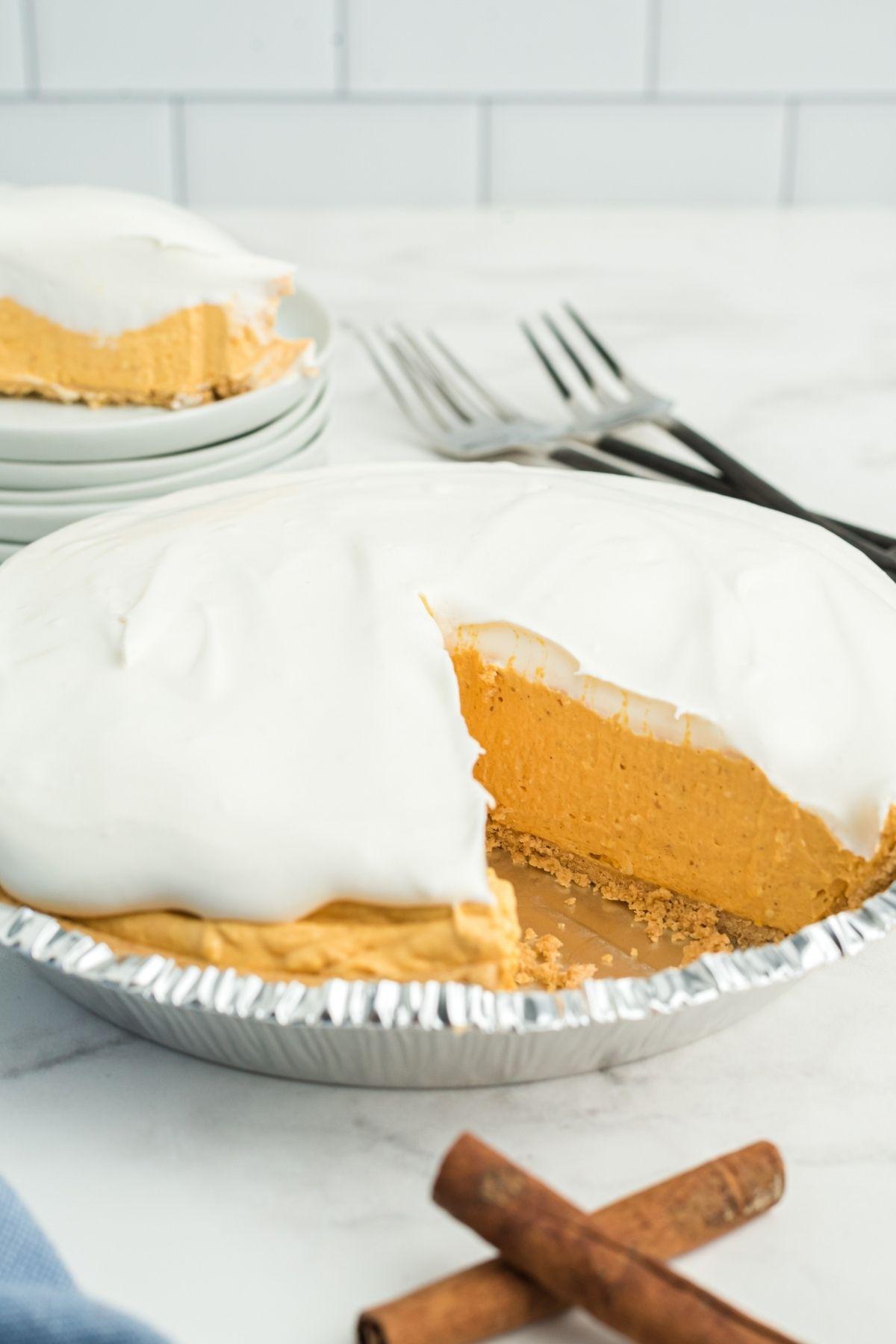 slice of pumpkin pie taken out of whole pie