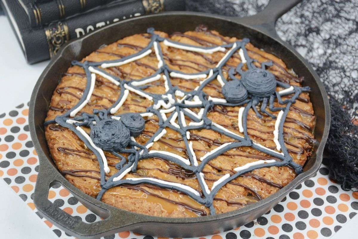 cookie in cast iron skillet with buttercream spider web and spiders