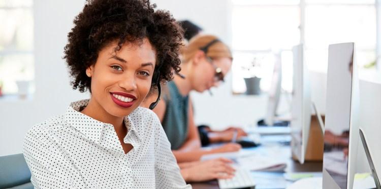 mulher negra olhando diretamente para câmera com um sorriso simpático
