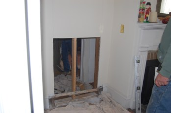 Wall to left of fireplace being opened up into doorway at the Ballentine-Spence House