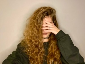 decorative picture: girl slowly sinking and hiding into her hair with her gaze dropped and shielded