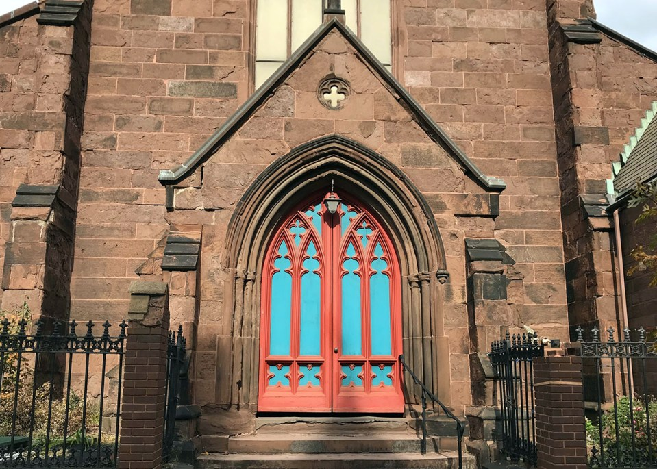 The entrance to a brownstone Gothic church building with a light blue and red door.