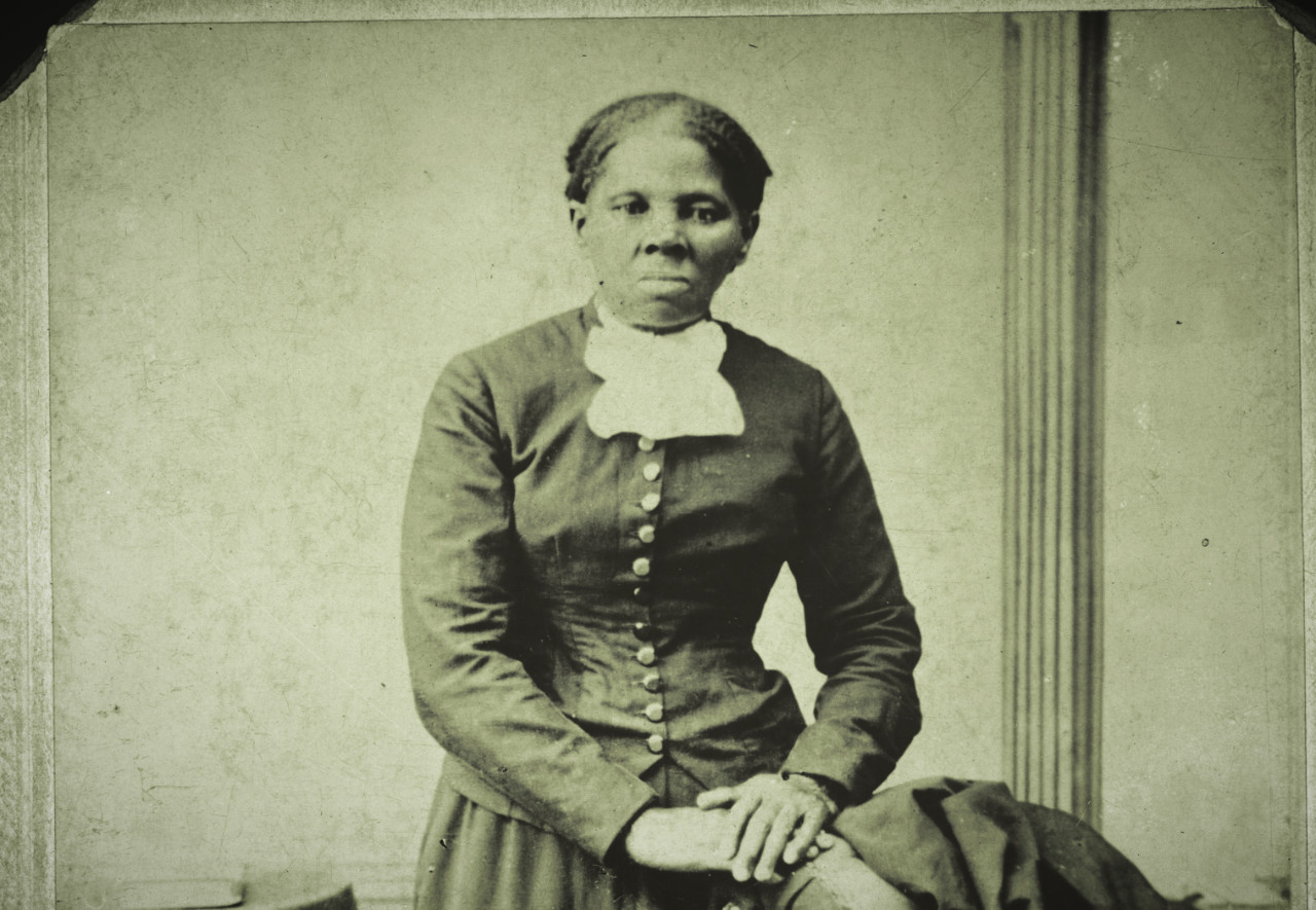 Black woman with short hair wearing a dark dresss seated for a portrait with her hands in her lap.