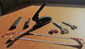 Sunlit cutting table with measuring table, scissors, weights, and a large stapler.