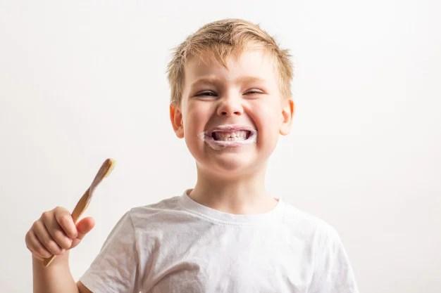 mignon garçon mignon posant avec brosse à dents en bambou sa bouche enfant brosse ses dents