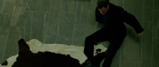 Bourne reels back from the hideous cowhide rug in Jarda's apartment... oh, and the dead guy.