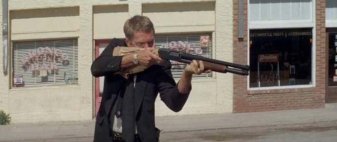According to IMDB, it was Steve McQueen's idea to have his character shoot and blow up a squad car.