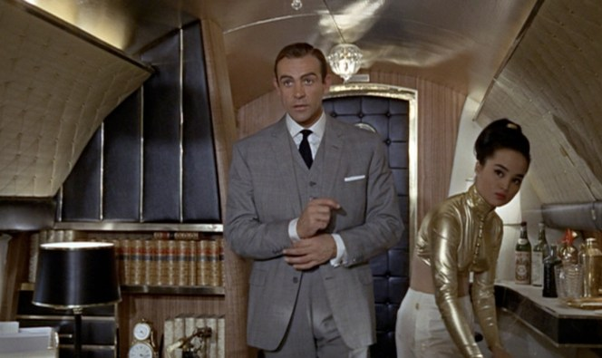"Yeah, I'm sure this is the last place Bond wants to be. A gold-plated plane, a martini-serving stewardess, a well-stocked bar at his disposal, and a rather attractive pilot. Give me a break. ""Prisoner"" my ass."