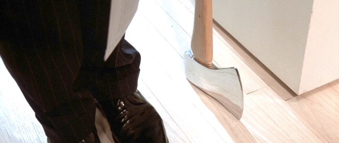 The shoes are shined to a degree almost as mirror-like as the axe.