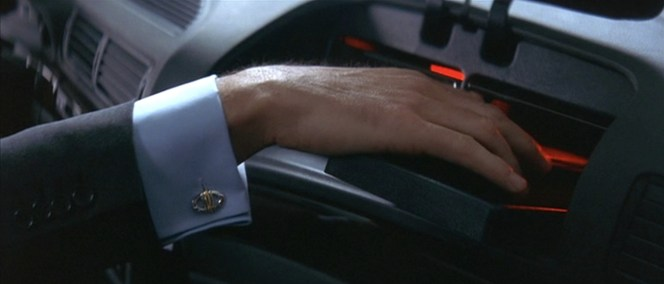 Bond takes the opportunity to show off his snazzy Dunhill cuff links as he reaches for his stored PPK.