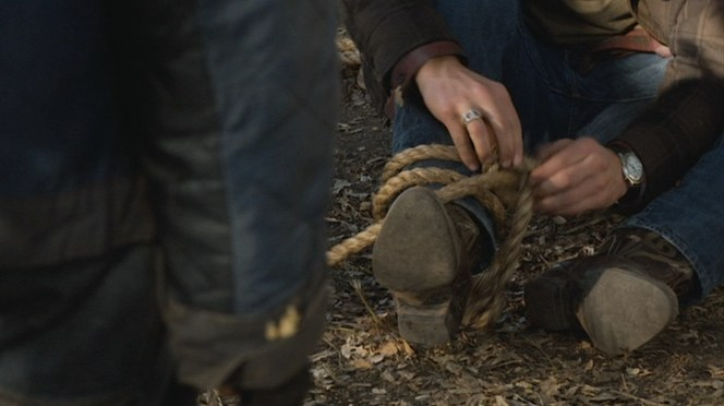 """Raylan's half-horseshoe ring and watch, seen as he unties the ropes from around his boots in """"Bloody Harlan"""" (Episode 2.13)."""