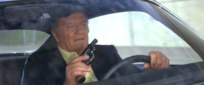 The force created from a .38 Special going off inside the close quarters of a Pontiac Trans Am would surely be enough to deafen. Luckily, John Wayne practices smart trigger safety.