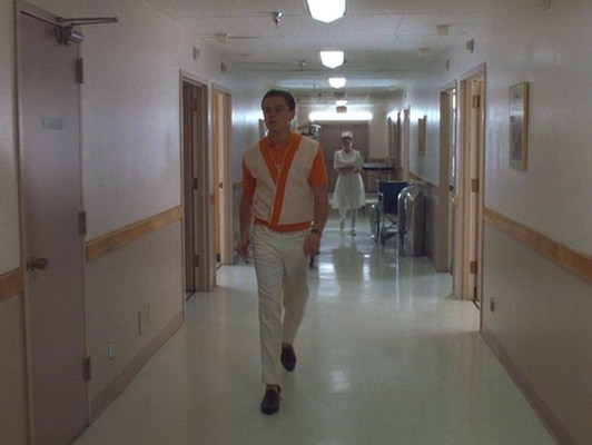 In his orange sherbet-inspired casual garb, Frank stands out against the hospital's pale beige-and-mauve color scheme.