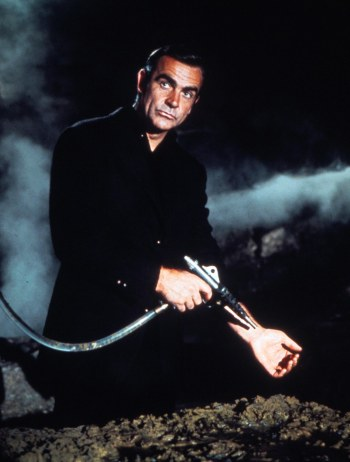 The color treatment in this publicity photo gives Bond the appearance of wearing all black clothing, as Sean Connery's Bond had previously done for covert assignments in Goldfinger and Thunderball.