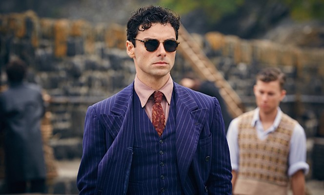 Production photo of Aidan Turner as Philip Lombard, showcasing the jacket's broad peak lapels and inner pockets as well as the four narrow-welted pockets of his waistcoat.