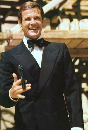 A chuckling Roger Moore twirls Bond's trademark PPK on set. Don't try this at home!