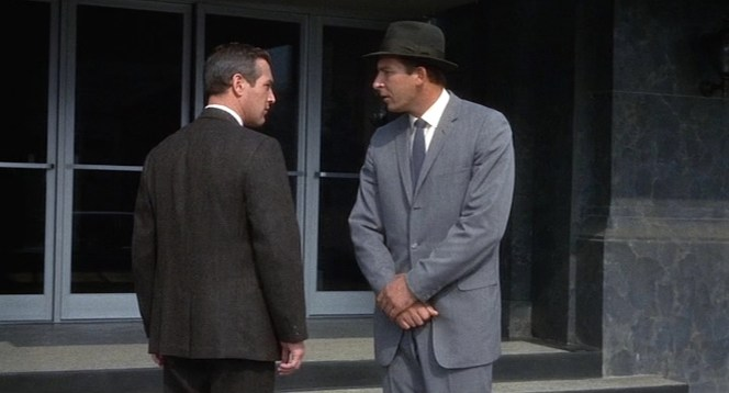 """A brown suit in the city? Surely you jest,"" the man in gray seems to be saying to our protagonist."